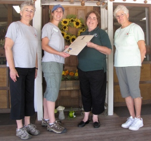"Mary Jordan (3rd from right) of the Department of Agricultural Resources presents Karen Green, Stephanie Waite, and Gail Conlin of Westward Orchards in Harvard, Massachusetts, a proclamation from Gov. Deval Patrick naming September ""Apple Month."" (Russell Steven Powell photo)"