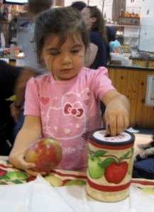 Aryana pays for her Cortland apple at the New England Apple Association booth in the Massachusetts Building at the Big E. New England's largest fair continues daily through Sunday, September 30. (Bar Lois Weeks photo)