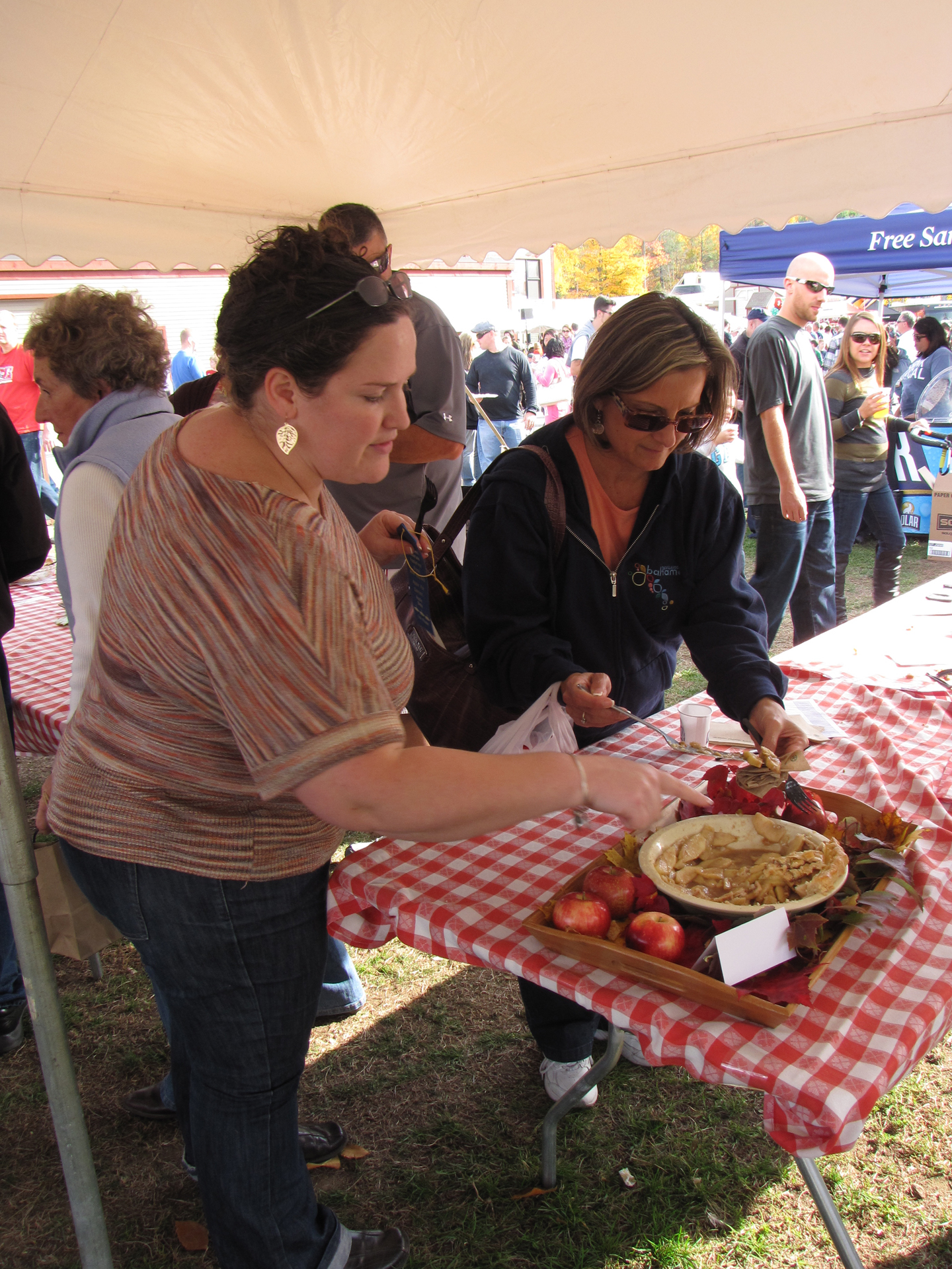 """Great New England Apple Pie"" winner Lori Meiners points to her pie as a spectator prepares to sample it after the judging. (Russell Steven Powell photo)"