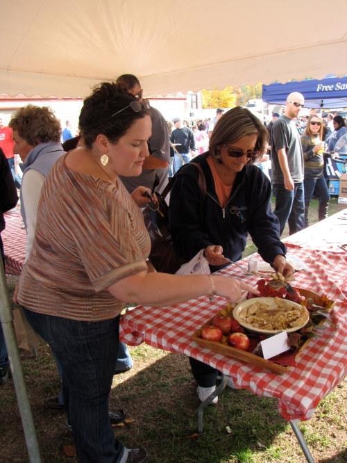 """Great New England Apple Pie"" winner Lori Meiners of Hubbardston, Massachusetts, points to her pie as a spectator prepares to sample it after the judging."